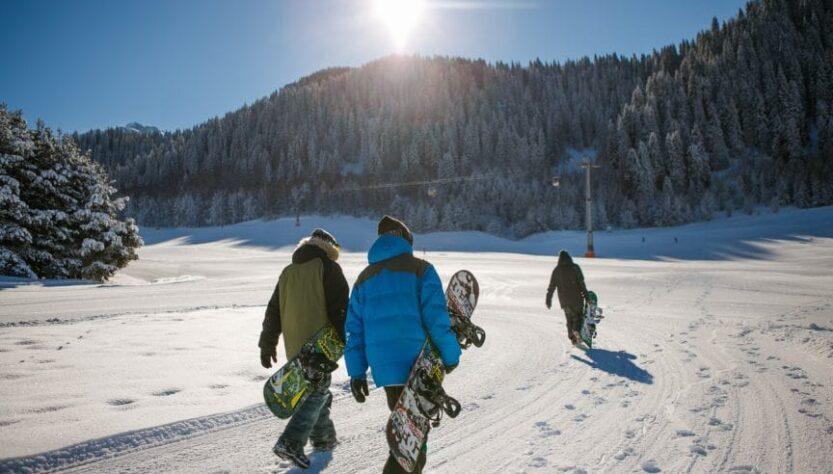 Three people playing snowboarding