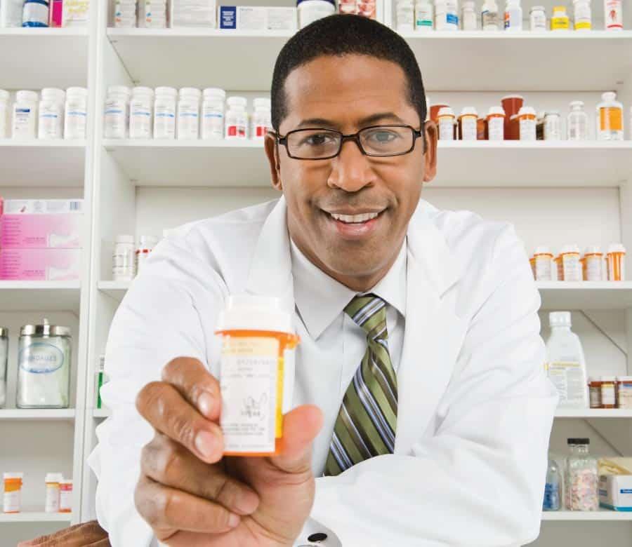 A doctor holding a bottle of medicine with a medicine shelf behind.