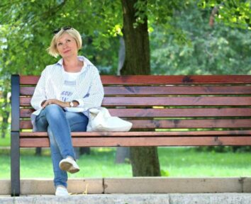 Breast cancer medication image- A woman sitting on a bench in a park.