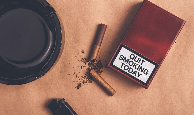Quit smoking today- a box of cigarette and lighter