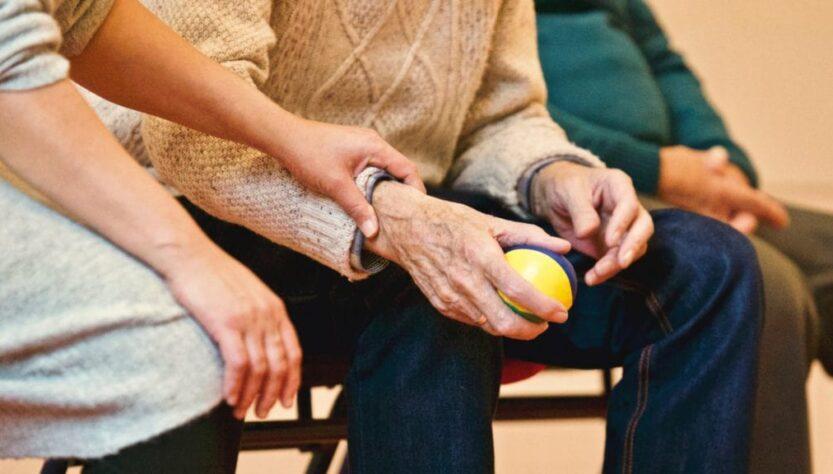 A senior person holding a ball.