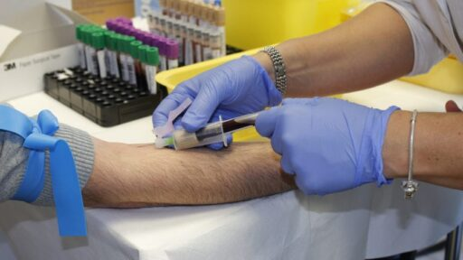 Blood Thinner Medication Image- a doctor taking blood of patient.