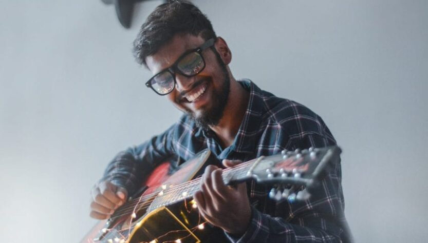 HIV TREATMENT BLOG IMAGE- A smilling man playing guitar.