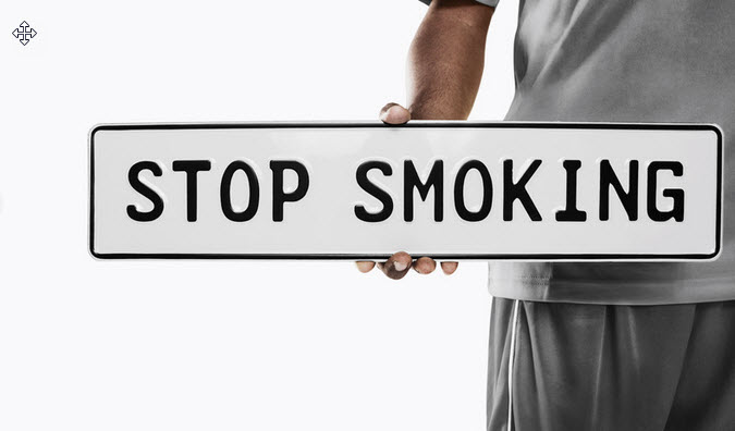 A person holding a Stop smoking sign.
