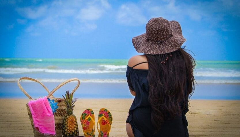 A lady sitting on the sand of beach