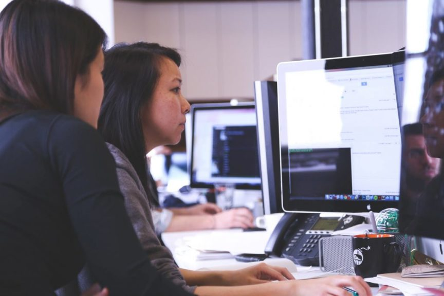 Two women working at the office in front on desktop