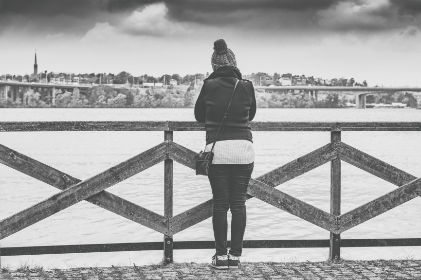 Woman anxiety- a woman standing alone beside a river- category image