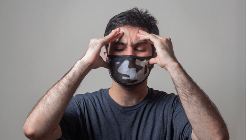 The man wearing mask and hold the head because of migraine
